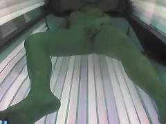 Girl masturbates while in a sunbed