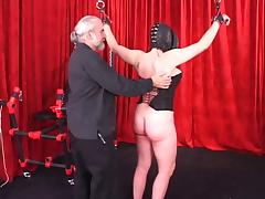 Spread-eagled shackled woman in leather mask and hood gets caned on her ass tube porn video