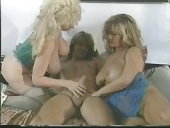 Blonde gets on bed and sucks massive cock while other girl fingering her pussy