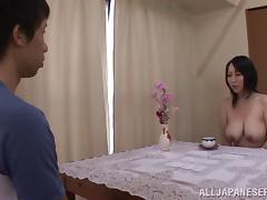 A hot, busty Japanese girl on her knees sucking a cock
