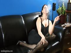 Brunette milf wearing stockings smokes a cig and fingers her twat