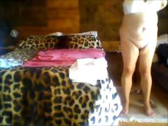 Chubby lies naked and then gets up to get dressed on her cam