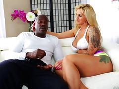 Tattooed blonde pornstar and her black stud get flirty in backstage interview