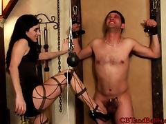 Hot brunette in black lingerie does painful stuff to naked male slave
