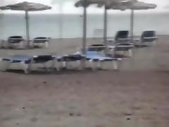 Milf sucks and jerks her man's cock at a beach on vacation