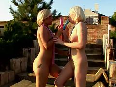 Two hot blondes sharing a double ended dildo outdoors