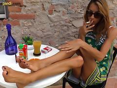 Smoking Italian girl models her pretty feet in close up