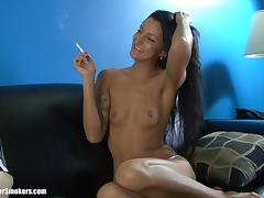 Flirtatious brunette with tattoos smoking on the couch solo