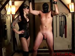 Fishnet-clad brunette with a sexy tattooed body torturing a stranger