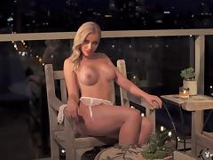Glamorous blonde chick shows off her huge tits on the balcony