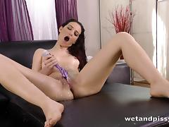 Brunette pissing on her couch and playing with the urine