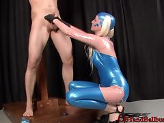 Latex-clad dominatrix with long blonde hair playing with a stranger's cock and asshole