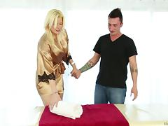 Golden haired masseuse pleasuring her regular client with a blowjob