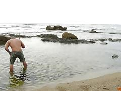 Very muscular couple has hardcore sex on rocks at the beach