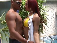 Sultry bikini-clad tranny with long red hair and big tits getting fucked in the ass