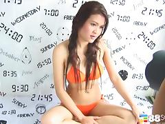 Model in an orange bikini shows off her natural titties