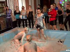 Fierce ladies wrestle violently at a muddy pool with a wild group of spectators