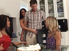Trio of tanned blonde's take down a lone cock in the kitchen in a foursome scene