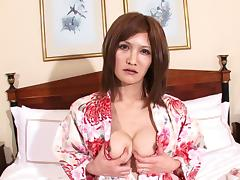 Japanese tranny with a small cock strokes erotically in bed