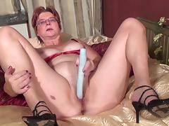Mature chick with glasses takes the long toy and penetrates herself