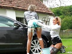 Right on the car's hood,two nasty lesbians enjoy washing and exposing their asses