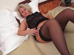 Hot blonde granny in stockings likes fingering her wet pussy