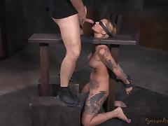 Deepthroating the blonde chick in the darkened BDSM dungeon