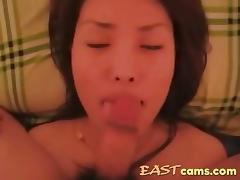 Pretty korean girl is filmed sucking a small cock and taking its cum all over her face.