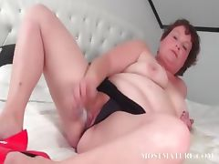 Mature slut pleasuring her pussy in bed