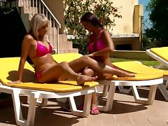 Two tanned lesbians in pink swimsuits having fun by the poolside