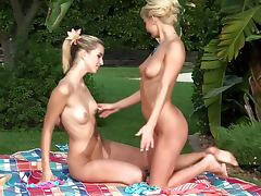 Beautiful blonde girls licking each other on the lawn