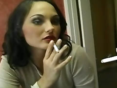 Sultry chick in the mirror smokes cigarette