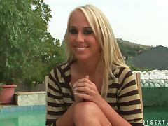 Blonde hottie Carla Cox gives an interview on the poolside