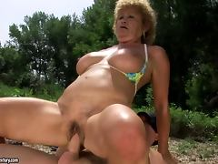Slutty granny Effie has sex with a lifeguard on a beach tube porn video