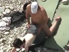 Lewd couple makes love on a nude beach in the presence of their friends