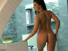Stunning brunette with fake tits walks naked around the house