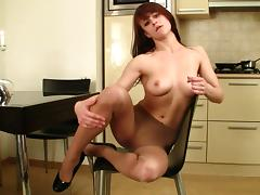 Slender redhead babe poses in the kitchen