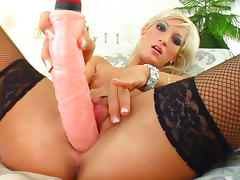 Busty blonde is stretching her trimmed puss with dildo