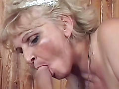 Hot mature blonde in stockings is giving a blowjob