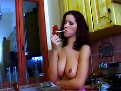 Curly-haired busty model is smoking a tasty cigerette