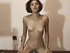 Slender brunette is stuffing her trimmed pussy on the floor