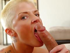 Busty blonde with tattoos is sucking a cock