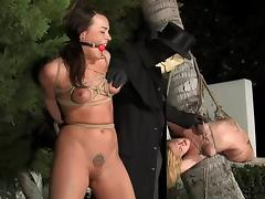 Two hot bitches enjoy being tormented in the yard in rough BDSM scene