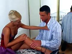 Sizzling Nicolette gives a footjob to muscled guy