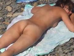 Sweet naked babes are lying on the beach