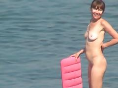 Sexy chick is walking naked on the beach