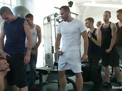 A tied up guy sucks huge dicks and get toyed in a gym tube porn video