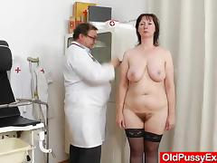 A mature woman in stockings gets examined by a doctor