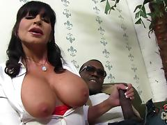 A huge breasted MILF strokes a big black cock in a backstage