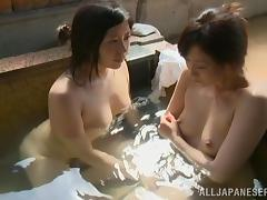 Two horny Japanese lesbians make out and pet each other in a sauna tube porn video
